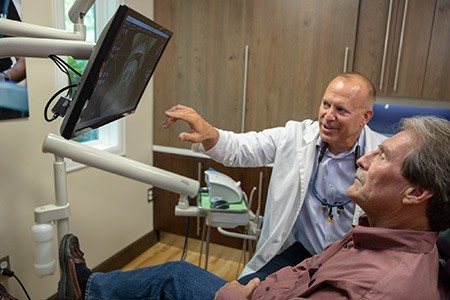Dentist and patient looking at computer monitor