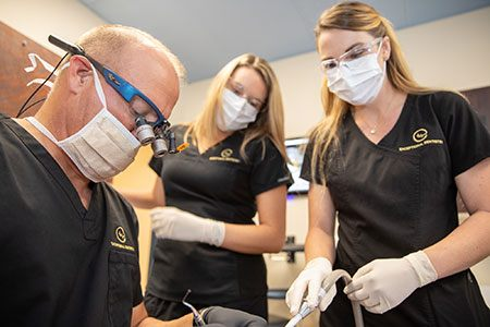 Dentist and two team members treating patient