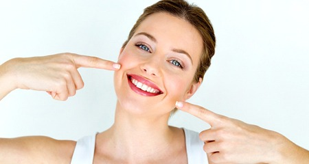 attractive woman pointing at perfect smile after dental bonding