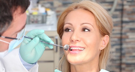 A woman having her teeth examined by a dentist