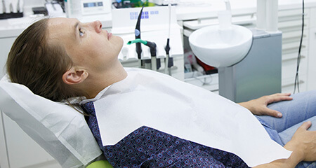 Relaxed patient under oral conscious sedation dentistry in dental chair