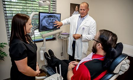 Dentist and patient looking at x-rays - Gainesville, Fl
