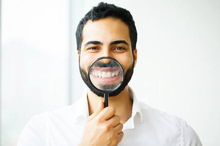 man holding magnifying glass up to his teeth after smile makeover