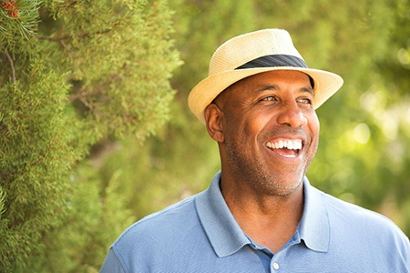 man in blue polo shirt and fedora smiling in the woods