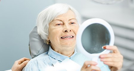 Woman looking at her smile after teeth X press dental implant tooth replacement